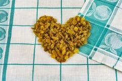 Gelbe Rosine zeichnete in Form eines Herzens auf einer Gewebeserviette Lizenzfreie Stockfotos