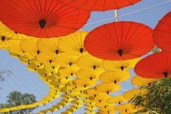 Gelbe, rote Papierregenschirm-Dekoration als Hintergrund stockfotografie