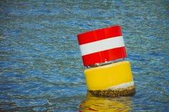Gelbe rote und weiße Stahlsich hin- und herbewegende Navigationsboje im Blauen Lizenzfreies Stockbild