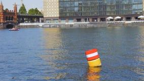 Gelbe rote und weiße Stahlsich hin- und herbewegende Navigationsboje im blauen GelageFlusswasser stock footage