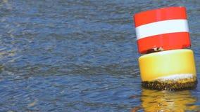 Gelbe rote und weiße Stahlsich hin- und herbewegende Navigationsboje im blauen GelageFlusswasser stock video footage