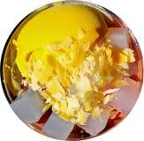 Gelbe runde Schaufel der MangoEiscreme mit dem quadratischen Kokosnussgeleebelag lokalisiert auf weißem Hintergrund lizenzfreie stockfotos