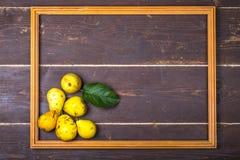 Gelbe Saisonbirnen mit Blatt im Holzrahmen auf dem backgroun Lizenzfreie Stockfotografie