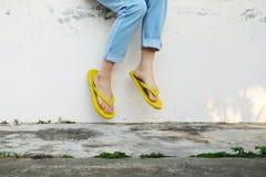 Gelbe Sandalen Frau, die Flip Flops und Blue Jeans stehen auf altem Zement-Boden trägt stockbilder