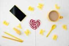 Gelbe Schale mit coffe, Herz formte Süßigkeit, Buchstaben, gelbes Telefon und Bleistifte auf weißem Hintergrund Platz für Text An Lizenzfreie Stockbilder