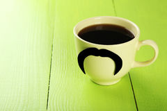 Gelbe Schale mit dem Papierschnurrbart und Kaffee auf grünem hölzernem Hintergrund Stockbilder