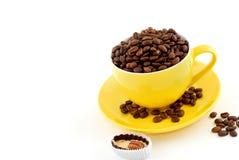 Gelbe Schale mit dem Saucer voll von den Kaffeebohnen Lizenzfreies Stockfoto