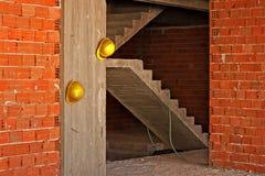gelbe Schutzhelme, die an der Betonmauer hängen Stockfotografie