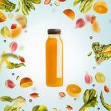 Gelbe Smoothie- oder Saftflasche mit Fliegen oder fallenden Bestandteilen: Zitrusfrüchte, Orangen und Beeren auf hellblauem Hinte lizenzfreie stockbilder