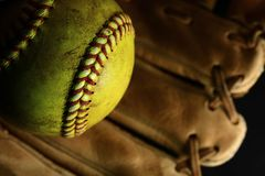 Gelbe Softballnahaufnahme mit Rotnähten auf einem braunen Lederhandschuh stockfoto