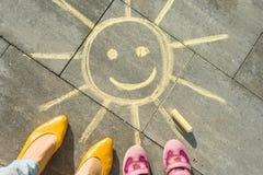 Gelbe Sonne und Füße der Frau und des Kindes Stockfoto