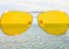 Gelbe Sonnenbrille auf dem Hintergrund des Meerwassers und des blauen Himmels Sonniger Tag, glückliche Ferien, guter Rest, Glück lizenzfreies stockfoto