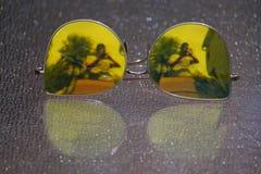 Gelbe Sonnenbrille nachgedacht über Glastisch lizenzfreies stockbild