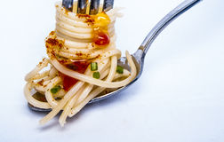 Gelbe Spaghettis auf einem Löffel und einer Gabel Stockbilder