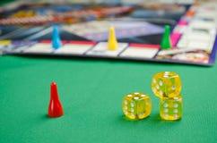 Gelbe Spielwürfel für Brettspiel auf einem grünen Hintergrund lizenzfreies stockbild