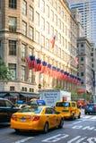 Gelbe Stadtfahrerhäuser in den Straßen von Manhattan mit amerikanischen Flaggen auf Gebäude im Hintergrund Stockfoto