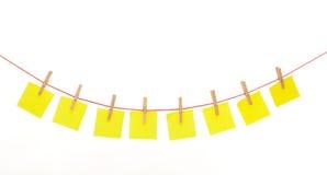 Gelbe stickies gehangen an das rote Seil lokalisiert Lizenzfreies Stockfoto