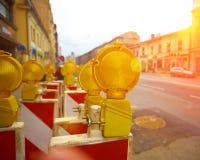 Gelbe Straßenarbeitenblitzgeber schließen oben mit Sonnenuntergangsonne und ehrfürchtigen Blendenflecken Lizenzfreie Stockbilder
