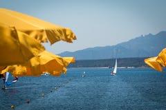 Gelbe Strandschirme in der Linie nahe Küstenlinie und weißem Segelboot Stockbild