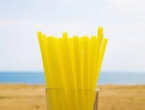 Gelbe Strohe in einem transparenten Glas auf dem Strand Stockbild