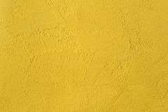 Gelbe strukturierte Wand. Hintergrund Stockfotografie