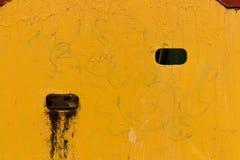Gelbe strukturierte Wand mit Löchern Stockfotos