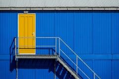 Gelbe Tür in einer blauen Fassade Stockbild