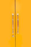 Gelbe Tür und glatte Griffe Lizenzfreies Stockbild