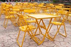 Gelbe Tabellen und Platz der Stühle im Freien Stockbild