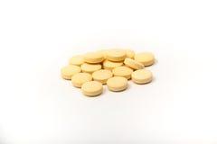 Gelbe Tabletten mit dem weißen Hintergrund Stockbilder