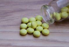 Gelbe Tabletten und Glasflasche auf einem hölzernen Hintergrund Stockfotografie