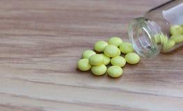 Gelbe Tabletten und Glasflasche auf einem hölzernen Hintergrund Stockfotos