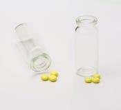 Gelbe Tabletten und leere Flasche stockfotografie
