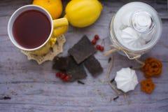 Gelbe Tasse Tee, Zitrone, Mandarine und Meringe auf dem Tisch Stockfotografie