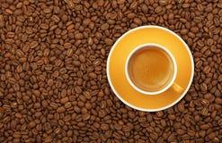 Gelbe Tasse und Untertasse des Espressos auf Kaffeebohnen Lizenzfreies Stockbild