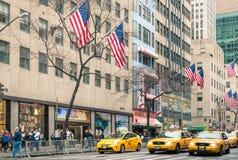 Gelbe Taxis und amerikanische Flaggen auf der 5. Allee - New York City Stockfoto