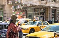 Gelbe Taxis und obdachloser Verkäufer in New York City Lizenzfreies Stockbild