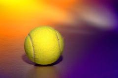 Gelbe Tennis-Sport-Kugel über purpurrotem Hintergrund Stockfotografie