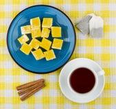 Gelbe türkische Freude in der Platte, in der Tasse Tee und im Zimt Stockbilder