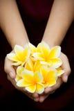 Gelbe tropische Blumen auf Händen lizenzfreies stockfoto