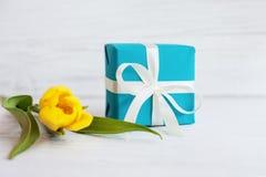 Gelbe Tulpe und ein Kasten mit einem Geschenk Konzept des Feiertags, Geburtstag lizenzfreies stockfoto