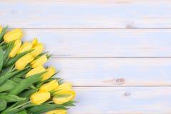 Gelbe Tulpen auf hölzernem Hintergrund mit Kopienraum Lizenzfreies Stockbild