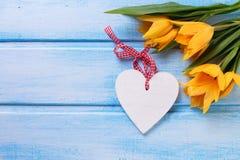 Gelbe Tulpen des Frühlinges und dekoratives Herz auf Blau malten woode Lizenzfreie Stockfotos
