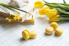 Gelbe Tulpen, gelbe Narzissen, alte Bücher und Zitronenmakronen auf einem hellen Hintergrund Lizenzfreie Stockfotografie