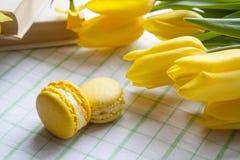 Gelbe Tulpen, gelbe Narzissen, alte Bücher und Zitronenmakronen auf einem hellen Hintergrund Lizenzfreie Stockbilder