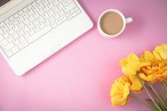 Gelbe Tulpen, Laptop und Kaffee auf einem lila Hintergrund entspringen, gelegte Draufsicht des Sommerkonzeptes Ebene stockbild