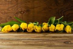 Gelbe Tulpen rudern auf hölzernem Hintergrund, kopieren Raum stockfotos