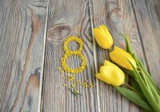 Gelbe Tulpen und die Tabelle acht Stockbild
