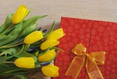 Gelbe Tulpen und Geschenk, die auf Holz liegt Stockfoto