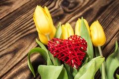 Gelbe Tulpen und handgemachtes rotes Herz Stockfotografie